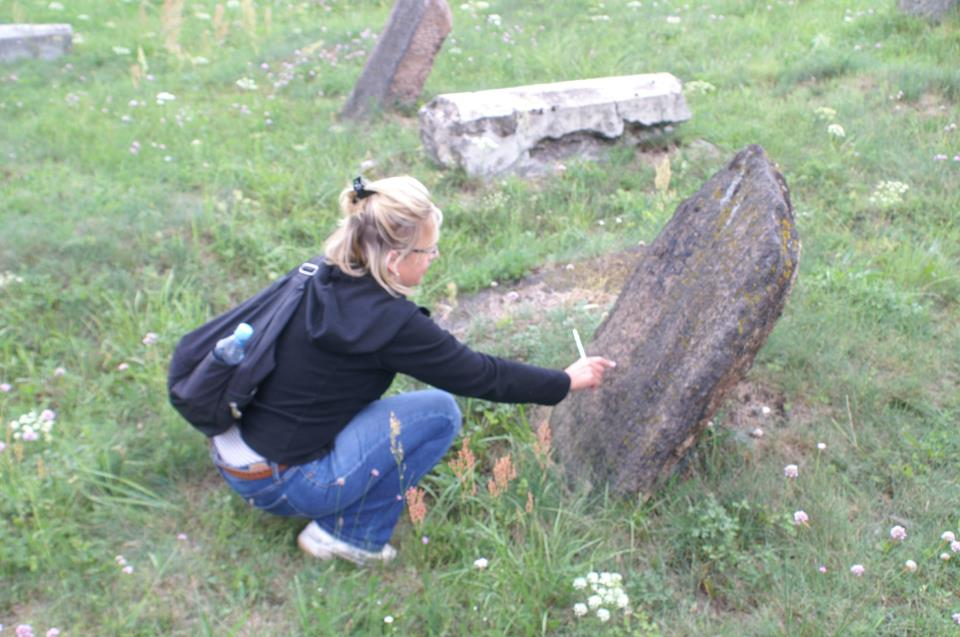 Dr. Heidi Szpek works on a gravestone in the Bagnówka cemetery